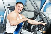 Smiling athlete bodybuilder man at biceps brachii muscles exercises with training dumbbells in fitne