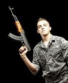 portrait of young soldier holding rifle wearing urban camouflage over black background