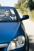 stock photo of luxury cars  - Front view of a young man driving his convertible car - JPG