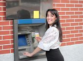Smiling beautiful woman withdrawing money from a cashpoint