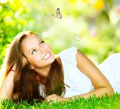 Spring Beauty Girl. Beautiful Young Woman Lying on Green Grass outdoor. Park. Meadow. Summer. Spring