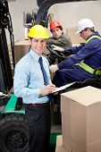 Portrait of supervisor writing on clipboard with foremen working at warehouse