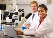stock photo of scientist  - Male And Female Scientists Using Microscopes In Laboratory - JPG