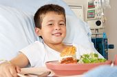 Boy Eating Meal In Hospital Bed