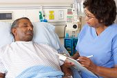 Nurse Talking To Senior Male Patient On Ward