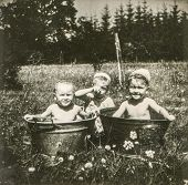 Vintage photo of little children bathing in wash tubs outdoor (early fifties)