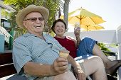 Portrait of cheerful senior couple sitting together with ice cream