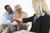 Senior African American couple seal a deal with their personal financial adviser at home