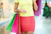 Female customer carrying colorful shopping bags