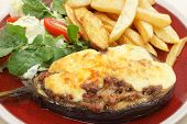 The Greek dish of aubergines stuffed with minced beef, onion and tomatoes, topped with bechamel sauce and cheese, served taverna-style with a salad of rocket, lettuce and tomato, and french fries