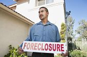 Young man holding 'Foreclosure sign' with house in the background