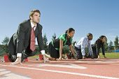 Full length of four multi ethnic businesspeople at starting position on race track