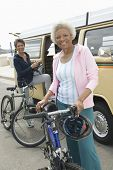 stock photo of campervan  - Portrait of happy senior women with bicycles and RV - JPG