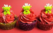 Three Christmas Cupcakes With Fun And Quirky Reindeer Face Toppings In Modern And Fun Festive Red An