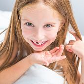 little girl showing her teeth that fell