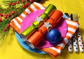 Bright And Colorful Christmas Table Setting With Plates, Forks And Knives, Christmas Bon Bons Cracke