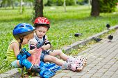 Little boy and girl in roller equipment sit on curb of walkway in summer park and feed pigeons with