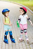 Little boy and girl in roller equipment stand on walkway in summer park