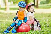 Little boy and girl in roller equipment sit together on red ball for jumping in summer park