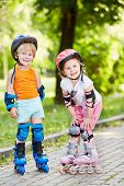 Smiling little boy and girl in protective equipments and rollers stand on walkway in summer park