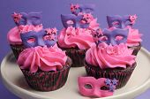 stock photo of masquerade  - Pink and purple masquerade masks decorated party cupcakes with pink frosting for teenage birthday New Years Eve or wedding bridal shower party - close up.