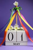 May Day, May 1, White Block Calendar With Maypole And Rainbow Color Ribbons And Flowers Against A Pu