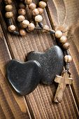 top view of stone hearts with rosary beads on wooden background