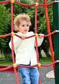 Young child playing on a red rope ladder.