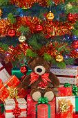 A handmade teddy bear wearing a bow in amongst gifts under a Christmas tree.