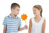 Peaceful brother and sister playing with pinwheel on white background