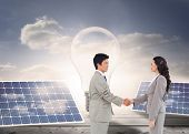 Composite image of side view of hand shaking trading partners in front of solar panels