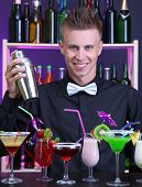 Portrait of handsome barman with different cocktails cocktail, at bar