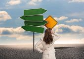 Composite image of businesswoman standing back to camera with hand on head in front of road signs