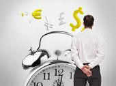 Composite image of businessman turning his back to camera in front of big clock on background