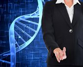 Composite image of businesswoman pointing at waist level next to dna spiral on blue background