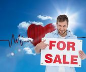 Composite image of smiling model holding a for sale sign in front of ecg line in sunny sky