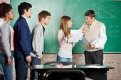 Mature teacher gesturing thumbsdown while looking at female student in classroom