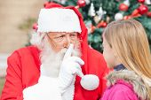 Santa Claus gesturing finger on lips while looking at girl outdoors