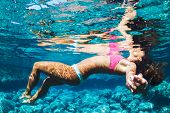 Beautiful Woman in Bikini Floating in Turquoise Colorful Water