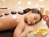 health and beauty concept - woman in spa salon with hot stones