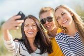 summer, holidays, vacation, happy people concept - group of friends taking photo picture with smartp