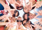 summer, holidays, vacation, happy people concept - group of teenagers looking down and showing finge