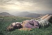 beautiful woman lying on the grass in the mountains