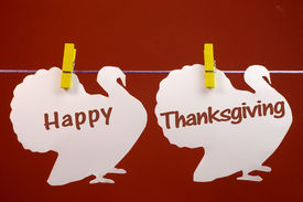 stock photo of pegging  - Celebrate Thanksgiving on the last Thursday in November with a Happy Thanksgiving message greeting written across white turkeys hanging from pegs on a line against a red brown background - JPG