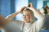 stock photo of scalping  - old caucasian woman applying lotion to prevent hair loss looking at mirror in bathroom - JPG