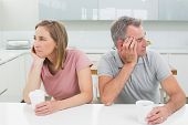 Unhappy couple not talking after an argument in the kitchen at home