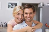 Close-up of a smiling young woman embracing man from behind in kitchen at home