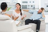 Angry couple sitting on couch talking to therapist in therapists office