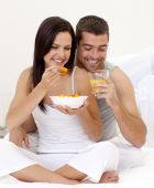 Woman And Man Having Nutritive Breakfast In Bed