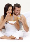 Couple Having Nutritive Breakfast In Bed